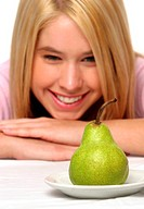 A girl resting her chin on her hands while looking at a plate of green pear