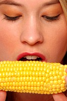 A woman looking down at a maize about to bite it