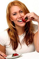A woman biting a strawberry
