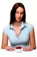 A woman sitting down looking at a bowl of strawberries