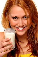 A woman holding up a glass of milk