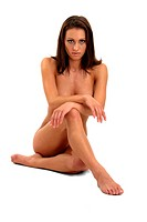A naked woman crossing her legs and hands covering her body