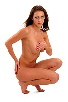 A naked woman squatting down with her hands covering her breasts and hip