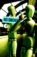 Dummy smoking cigarette in front of a no smoking sign
