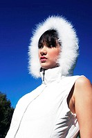 A woman in white sleeveless blouse and a furry hood