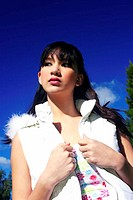 A woman in white sleeveless vest and furry hood posing outdoor (thumbnail)
