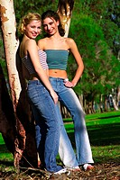 Two woman in tube tops and jeans standing beside a tree