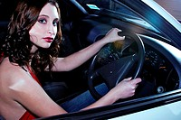 A woman in red halter neck sitting in a car holding the steering wheel