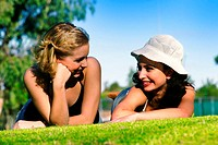 Two women lying on the grass talking