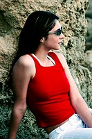 A woman in red sleeveless top and wearing sunglasses leaning on a tree