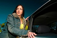 A girl in a denim jacket leaning against a car