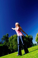 A blonde hair woman spreading her hands at a park (thumbnail)