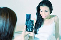 Woman using a digital camera to capture her friend's picture