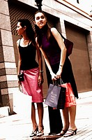 Two friends waiting for a taxi after shopping