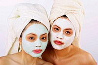 Two women with towel wrapped hair wearing a facial mask