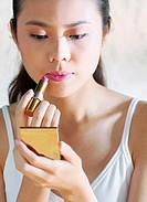 Woman looking at the compact mirror while applying lipstick on her lips