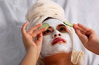 Woman with towel wrapped hair doing facial mask