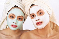 Two women with towel wrapped hair doing facial mask