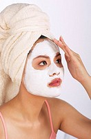 Woman with towel wrapped hair applying facial mask on her face