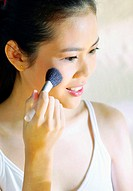 Woman brushing some blusher on her cheek