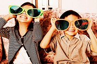 Boy and girl wearing big sunglasses