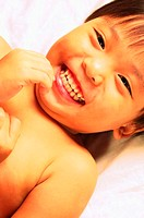Boy lying on the bed laughing