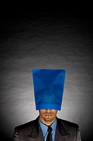 Businessman covering his head with a folder.