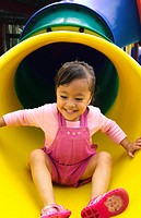 Girl sliding down a slide