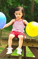 Girl holding two balloons