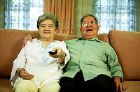 Old couple watching movie at home