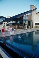 Family playing with a ball near a swimming pool