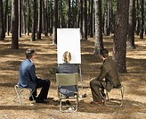 Office workers with flipchart in forest