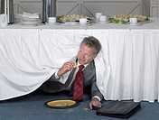 Businessman eating in secret