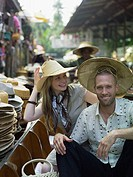 Couple trying on hats at floating market