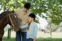 Father and daughter horseback riding