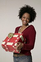 Woman with frizzy hair holding large gift, posing