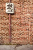 One way sign against brick wall on side walk