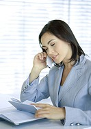 Businesswoman using cell phone and looking at agenda