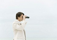 Businessman using binoculars, sea in background