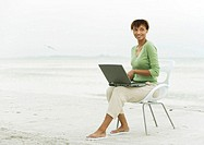 Woman on beach, sitting in chair using laptop