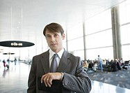 Businessman checking time in airport, looking at camera