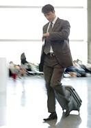 Businessman checking watch as he walks through airport, blurred motion