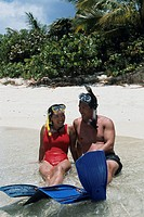 Couple in snorkelling gear reclining in surf on beach