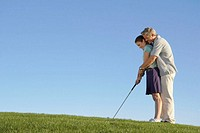 Mature man teaching mature woman how to golf, side view