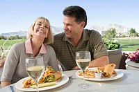Mature man and woman eating at table beside golf course, laughing