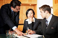 Businesswoman flanked by businessmen pointing at paperwork