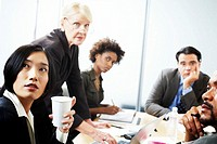 Senior businesswoman leading meeting by woman holding disposable cup