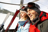 Couple riding in ski lift, smiling