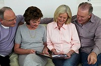 Two mature couples sitting on sofa looking at photo album, smiling