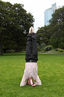 Young businessman doing headstand in park